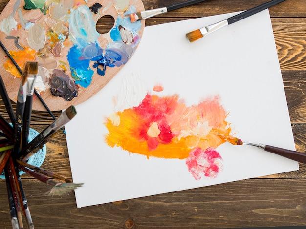 Vista dall'alto della tavolozza di colori con pennelli