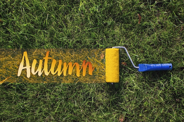 Top view of a paint roller painting a grassy strip using orange color with text autumn.