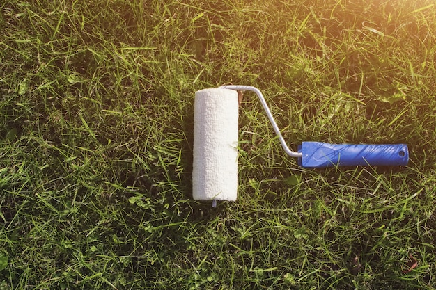 Top view of a paint roller with an blue handle, that is painting a grassy strip using lawn as color.
