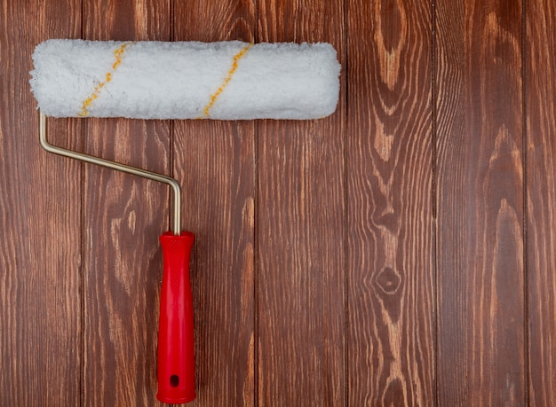 Top view of paint roller on wooden background with copy space