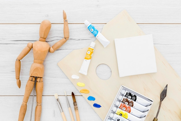 Top view paint supplies with wooden mannequin