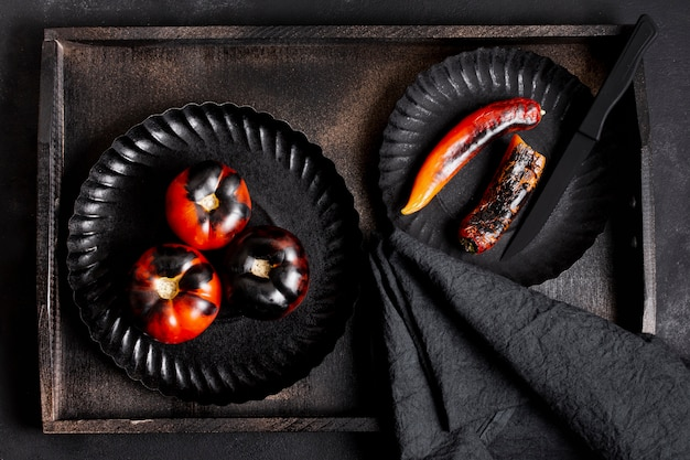 Top view painted black baked tomatoes and chilli peppers