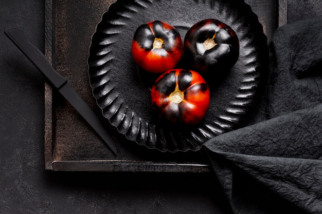 Top view painted black baked tomatoes on plate