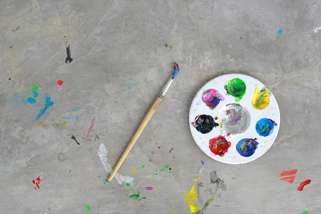 Top view of painted brush, palette and water paint on dirty cement floor.