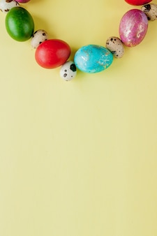 Top view painted eggs easter frame in circle shape on a yellow background. copy space