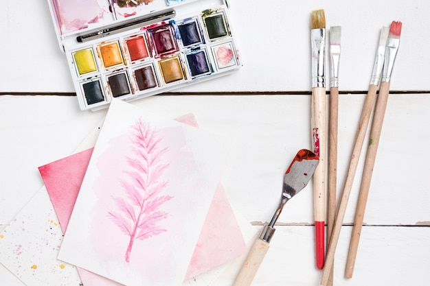 Top view of painting essentials with brushes and palette