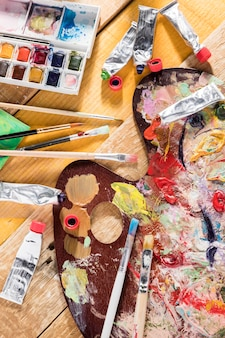 Top view of painting essentials with tubes and brushes