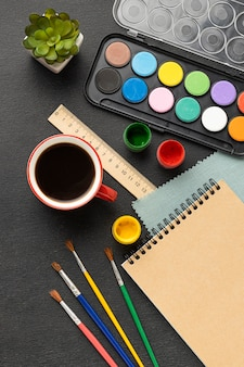 Top view of painting set with palette and coffee