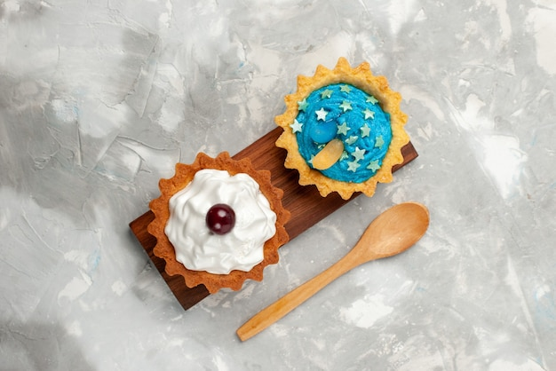 Top view pair of cakes with cream and wooden spoon on light background cake sweet biscuit cream