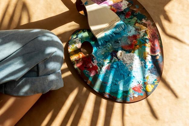 Вид сверху палитра с краской и кистью