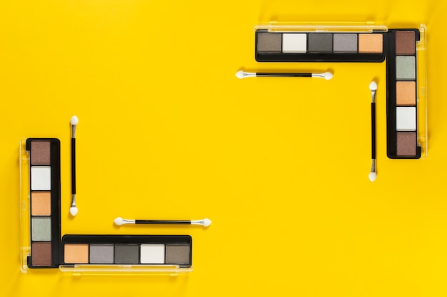 Top view of palettes on yellow background with copy space
