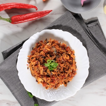 Top view pampis tongkol, manado's traditional seafood dish of spicy shredded fish, served on white ceramic
