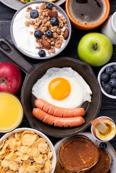 Top view of pan with egg and sausages surrounded by breakfast food