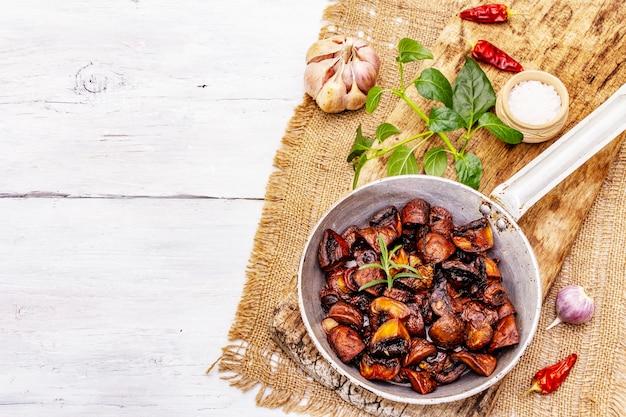 Сковорода вид сверху с жареными коричневыми шампиньонами и грибами