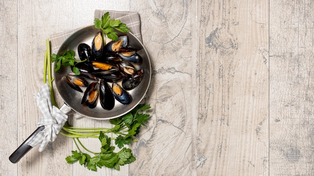 Top view pan with tasty mussels and parsley