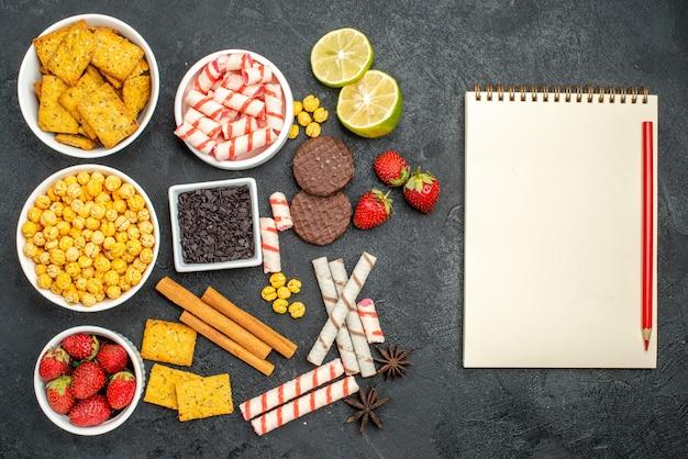 空きスペースのある黒い表面の空白のノートブックペンの近くに新鮮なレモンとスタウベリーが入った上面図の可食性スナックレシピ