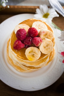 Top view pancake tower with banana and raspberries
