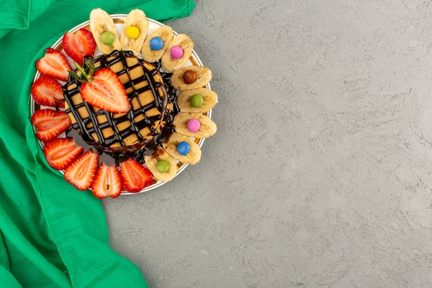 Top view pancakes along with poured chocolate sliced strawberries and bananas on the light