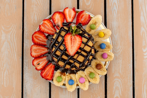 Top view pancakes chocolate with sliced red strawberries and bananas on the wooden floor