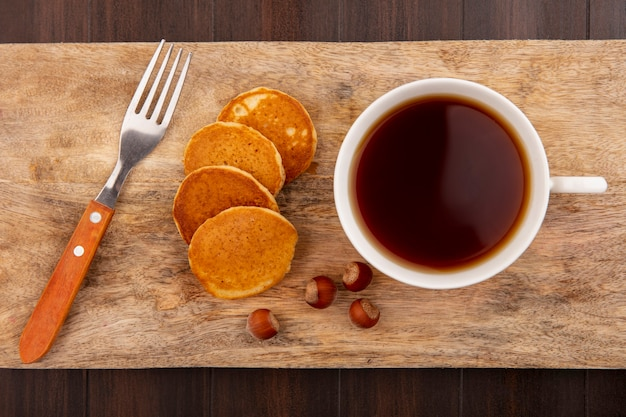 Top view of pancakes and cup of tea with nuts and fork on cutting board on wooden background