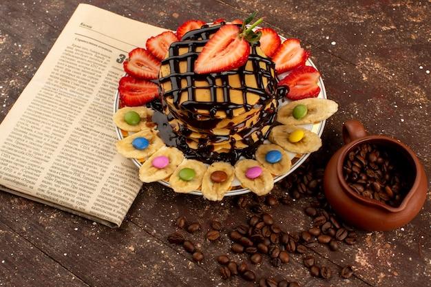 Vista dall'alto pancake deliziosi deliziosi con frutta fresca a fette e cioccolato sul pavimento marrone