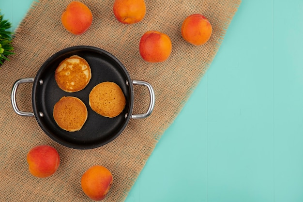 Top view of pancakes in pan and apricots on sackcloth on blue background with copy space