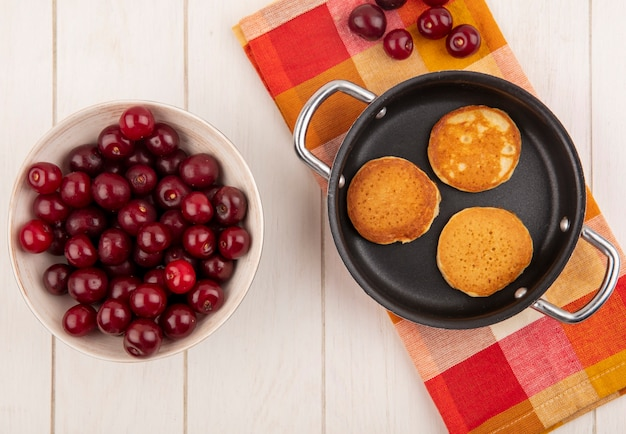 Top view of pancakes in pan and cherries on plaid cloth and in bowl on wooden background