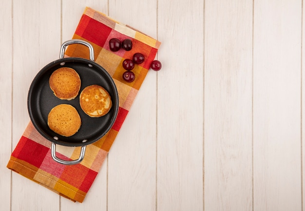 Top view of pancakes in pan and cherries on plaid cloth and wooden background with copy space