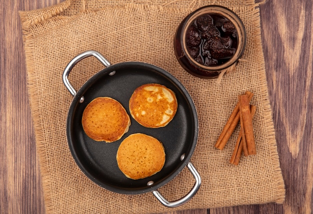 Top view of pancakes in pan and jar of strawberry jam with cinnamon on sackcloth on wooden background