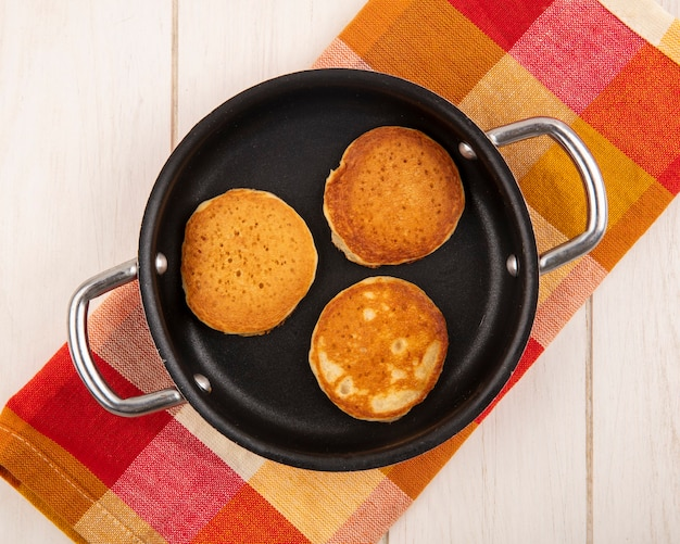 Top view of pancakes in pan on plaid cloth and wooden background