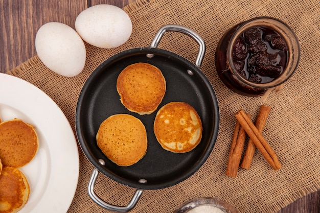 Top view of pancakes in pan and in plate and jar of strawberry jam with cinnamon and eggs on sackcloth on wooden background