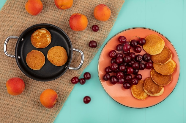 Top view of pancakes in pan and in plate with cherries and apricots on sackcloth and on blue background