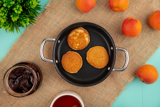 Top view of pancakes in pan and strawberry jam tea apricots on sackcloth on blue background