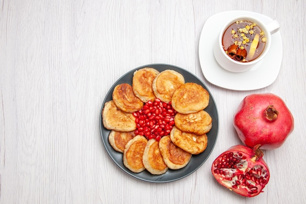 Top view pancakes and pomegranate plate of appetizing pancakes pomegranate and a cup of herbal tea on the table