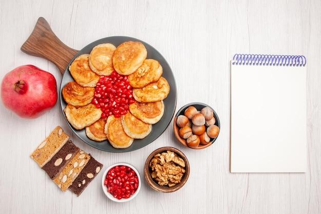 Vista dall'alto frittelle e melograno al melograno accanto al quaderno bianco ciotole di marmellata e nocciole piatto da torta di frittelle e semi di melograno sul tagliere di legno sul tavolo