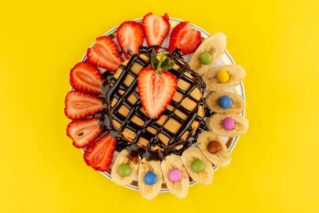 トップビューパンケーキ甘いおいしいおいしいスライススライスした赤いイチゴと黄色のプレート内のバナナ