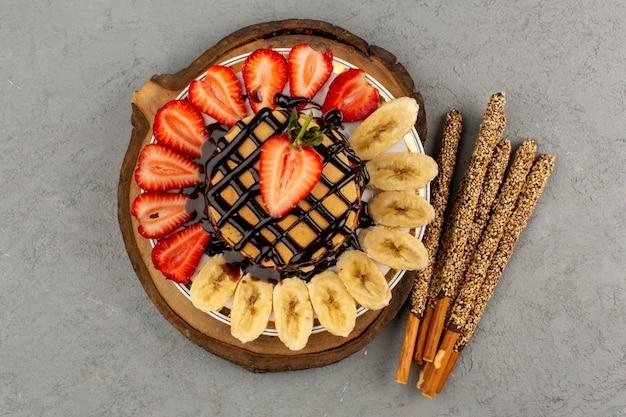 Вид сверху блины сладкие вкусные вкусные с нарезанной красной клубникой и бананами внутри белой тарелки на сером полу