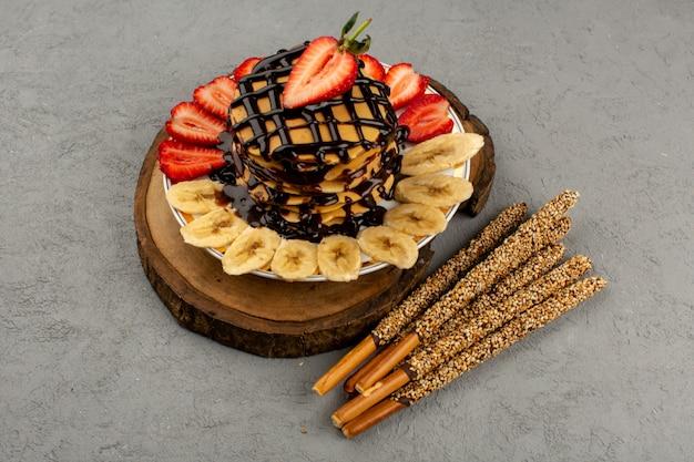 Vista dall'alto frittelle dolci deliziosi deliziosi con fragole rosse a fette e banane insieme a bastoncini di zucchero sul grigio