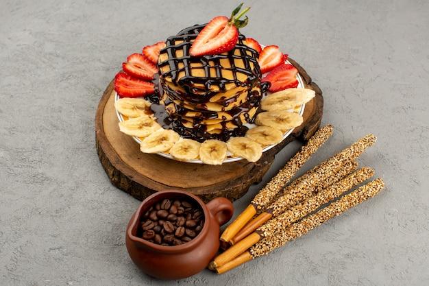 Vista dall'alto frittelle dolci deliziosi deliziosi con fragole rosse a fette e banane all'interno del piatto bianco sul pavimento grigio