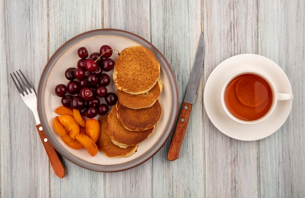 Top view of pancakes with apricot slices and cherries in plate and cup of tea on saucer with fork and knife on wooden background