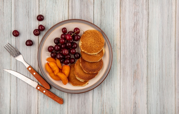 Top view of pancakes with apricot slices and cherries in plate with fork and knife on wooden background with copy space