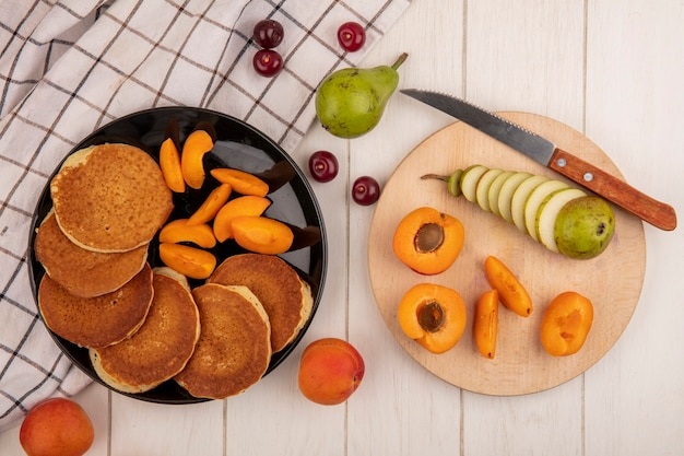 Top view of pancakes with apricot slices in plate and pear cherries on plaid cloth and sliced cut apricot and pear with knife on cutting board on wooden background