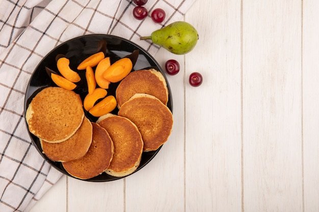 Top view of pancakes with apricot slices in plate and pear cherries on plaid cloth and wooden background with copy space