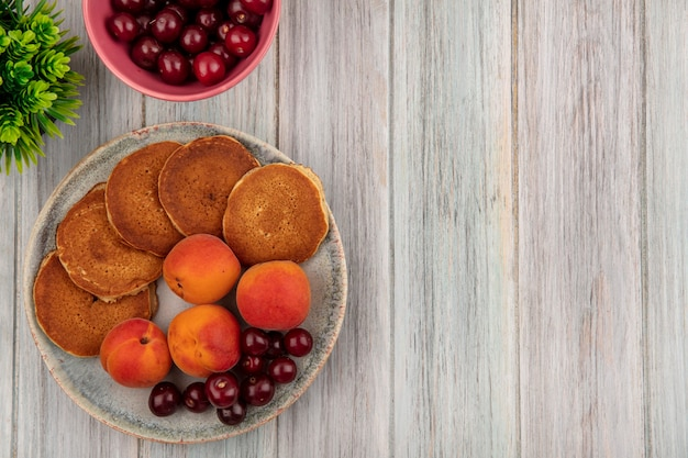 Top view of pancakes with apricots and cherries in plate and bowl of cherries on wooden background with copy space