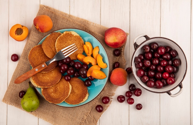 Top view of pancakes with cherries and apricot pieces in plate and apricots cherries pear on sackcloth and bowl of cherries on wooden background