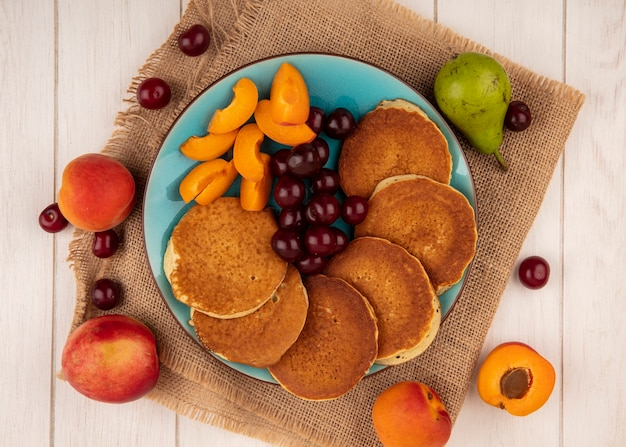 Top view of pancakes with cherries and apricot pieces in plate and apricots cherries pear on sackcloth and on wooden background