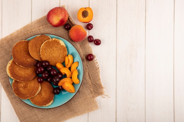 Top view of pancakes with cherries and apricot pieces in plate and apricots cherries on sackcloth and on wooden background with copy space