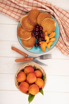 Top view of pancakes with cherries and apricot pieces in plate on plaid cloth and basket of apricots with fork and knife on wooden background