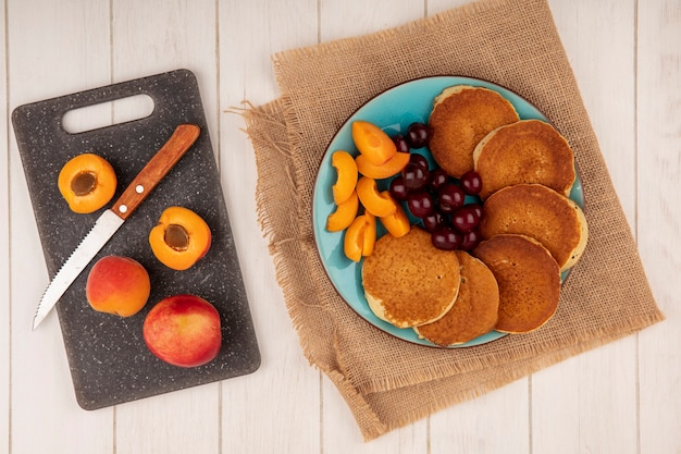 Top view of pancakes with cherries and apricot pieces in plate on sackcloth and apricots with knife on cutting board on wooden background