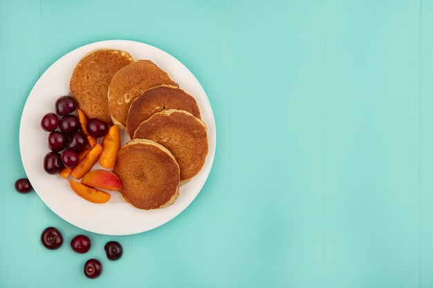 Top view of pancakes with cherries and apricot slices in plate on blue background with copy space